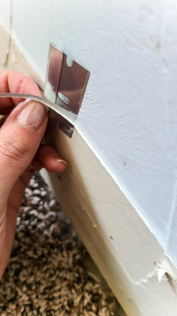 cutting away old paint from the wall with a razor blade