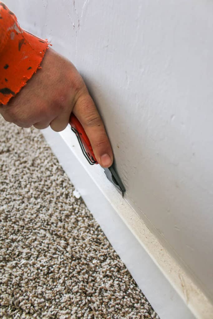 using a utility knife to cut caulk between a baseboard and wall