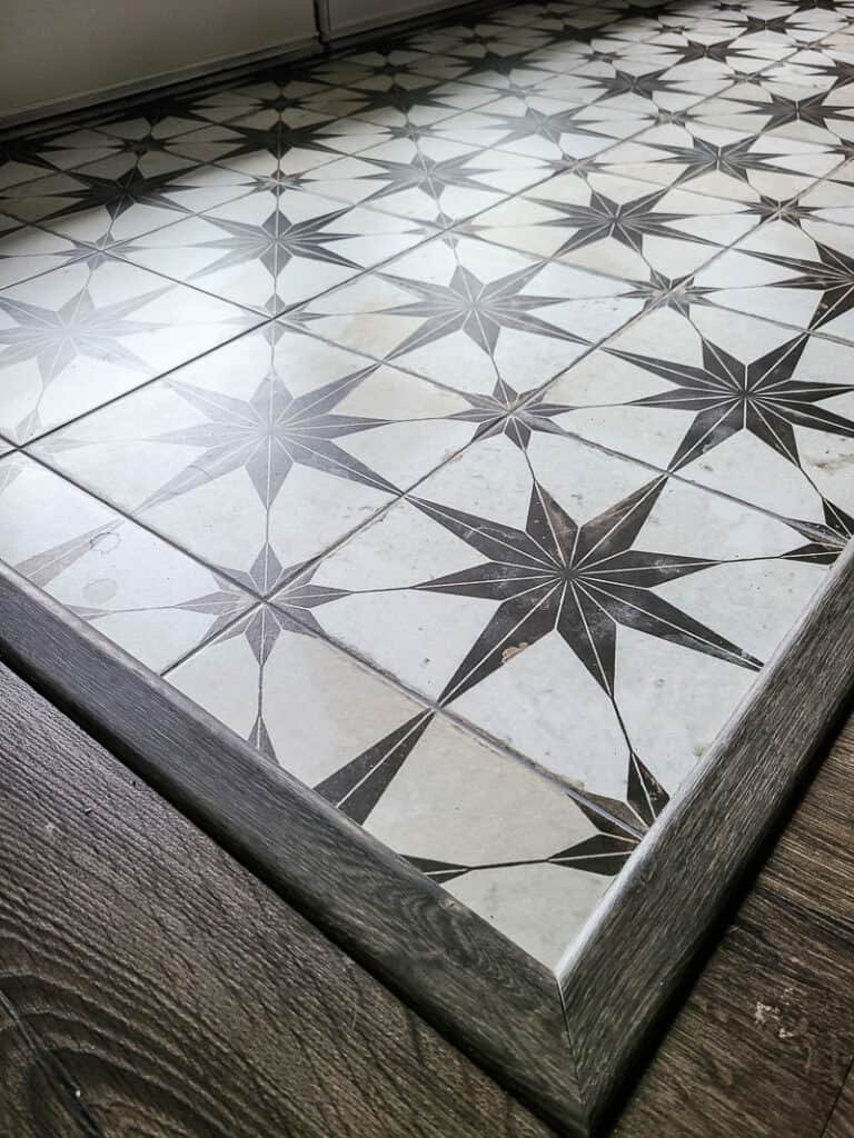 Small entryway with newly installed floor tiles with boho star pattern