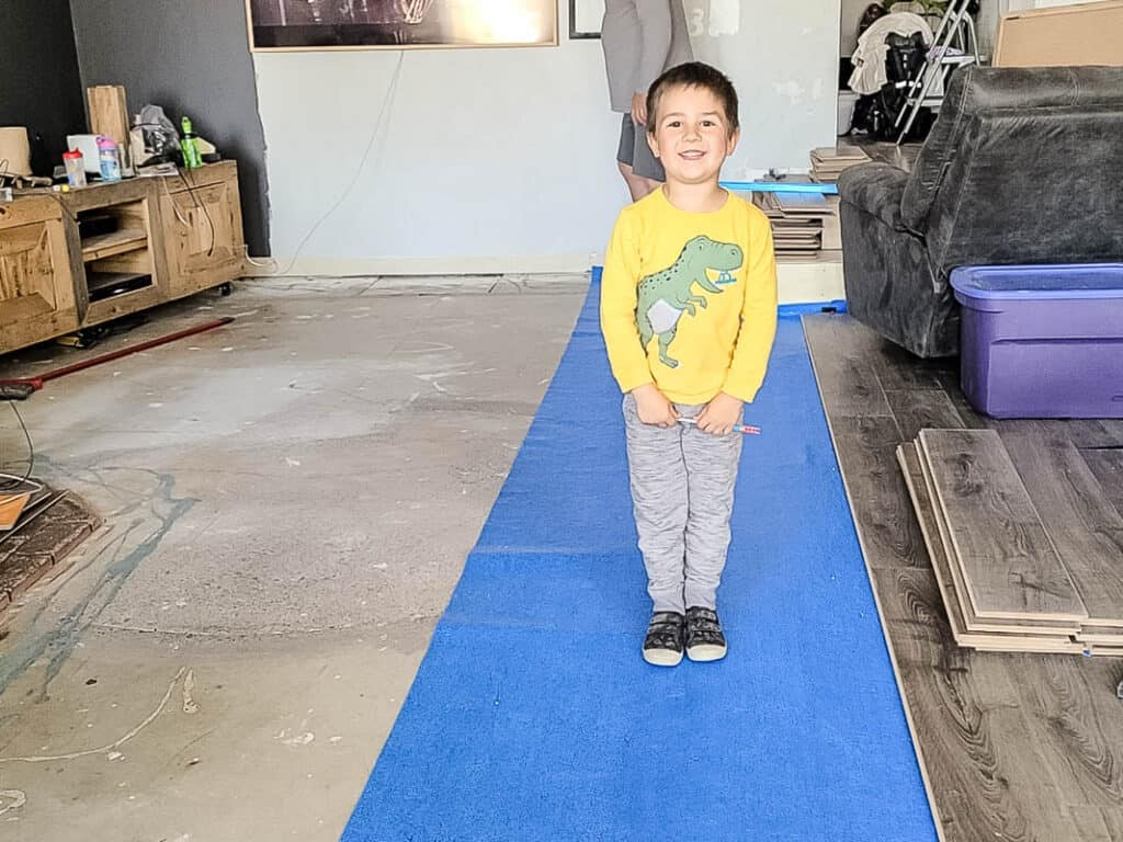 Boy wearing yellow sweater and pants standing on the standing in the underlayment and undone laminate flooring and uncovered concrete floor
