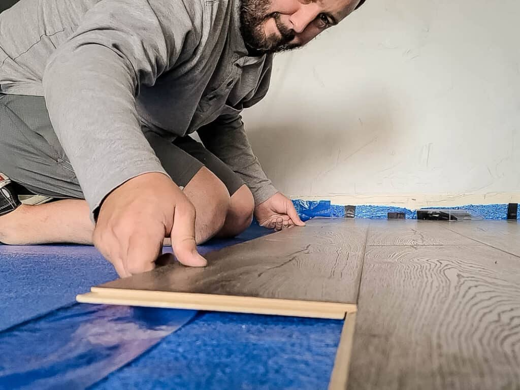 Man carefully placing the laminate beside the attached laminate floors on top of underlayment and clicking it into place