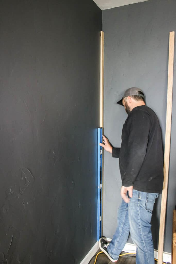 Man installing first wood slat with a level onto wall