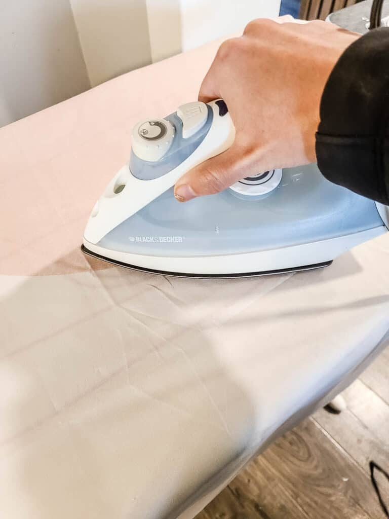 Woman ironing the fabric tapestry using electric iron