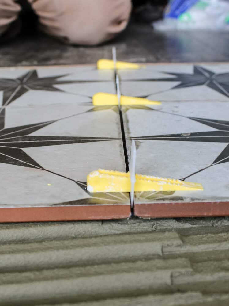 Floor tiles attached with spacers and clips on top of the floor with mortar