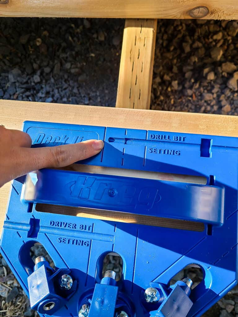 Woman pointing to the deck jig on top of the wood showing how to line up the deck jig to the joists in the deck frame