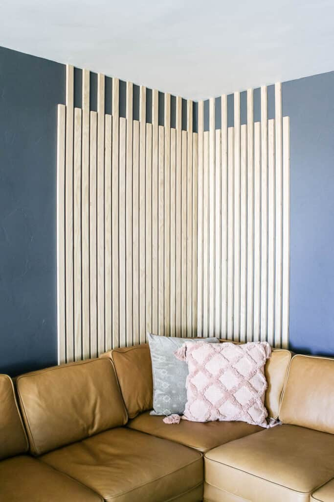 Wood slats as accent wall in the living room with dark gray walls with the leather couch and boho throw pillows