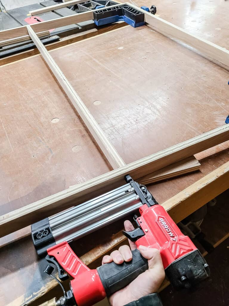 Assembling wood frame for tapestry using nail gun attaching the edges