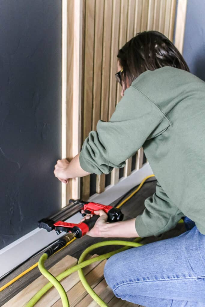 Woman holding a brad nailer attaching the wood slats on the wall