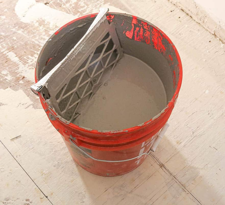 If you're doing a lot of painting, it may make sense for you to purchase your paint in 5 gallon buckets instead. If you do that you can hang a grate in the bucket to roll off excess paint like this.
