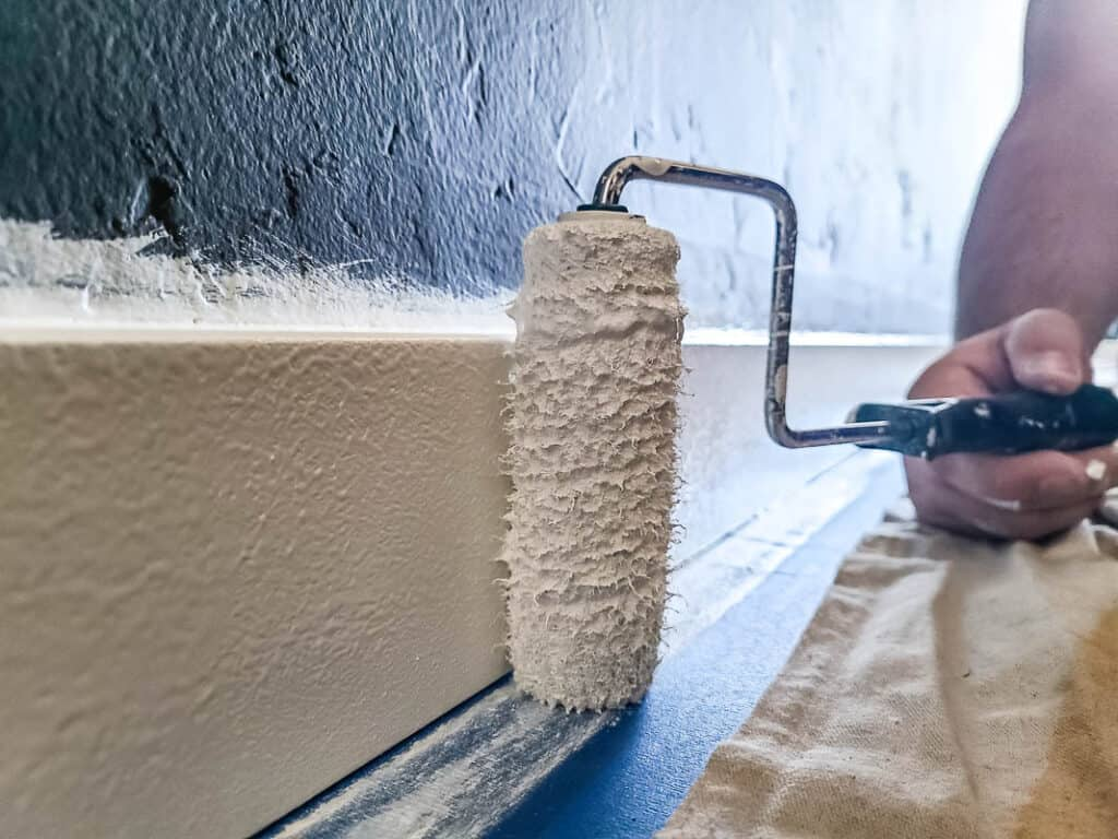 Man holding a paint roller painting the baseboards and trim with white paint