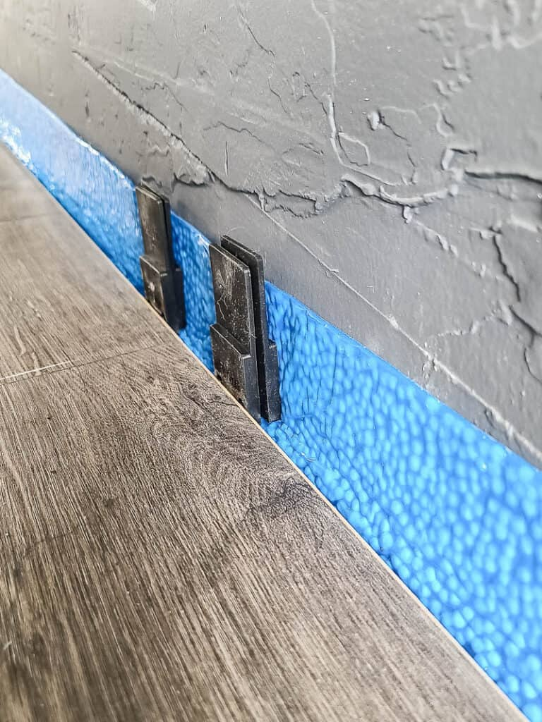Laminate floor attached with spacer between wall for expansion gap