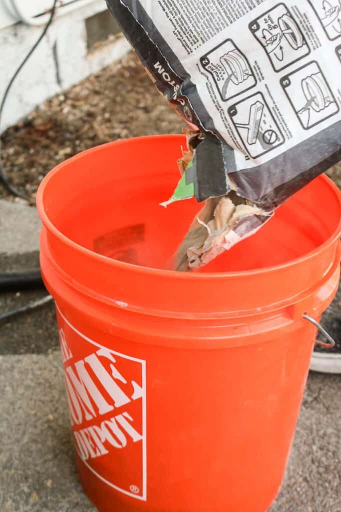 bag of thinset mortar being poured into orange bucket before being mixed