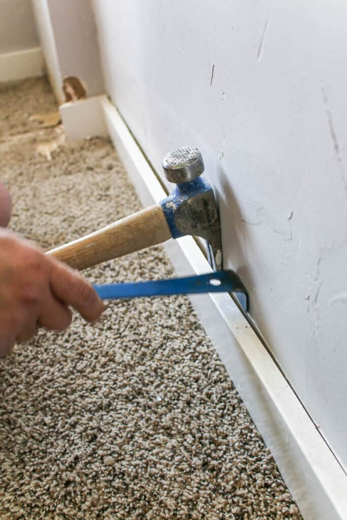 pronged end of a hammer and pry bar between the baseboard and wall