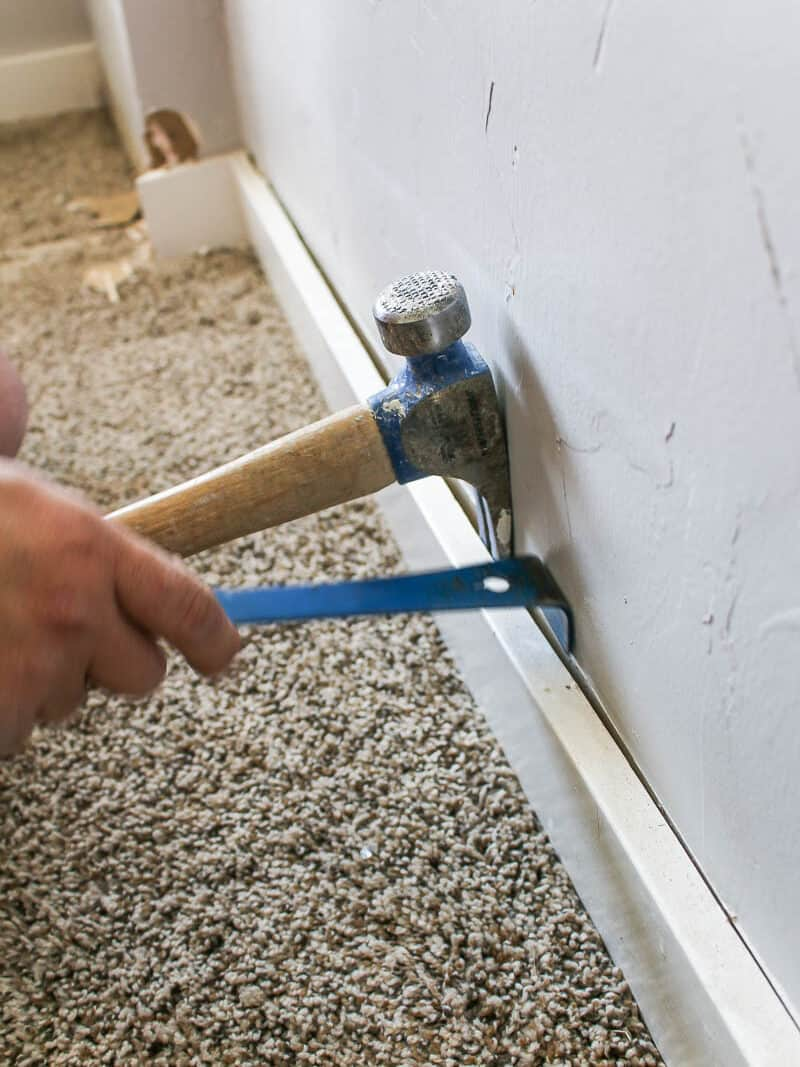 Man holding a mallet and pull bar removing the trim of the room