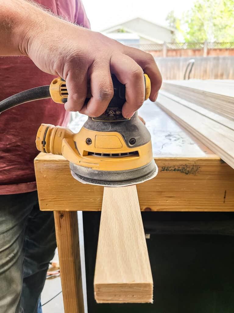 Man holding orbital sander sanding wood slat