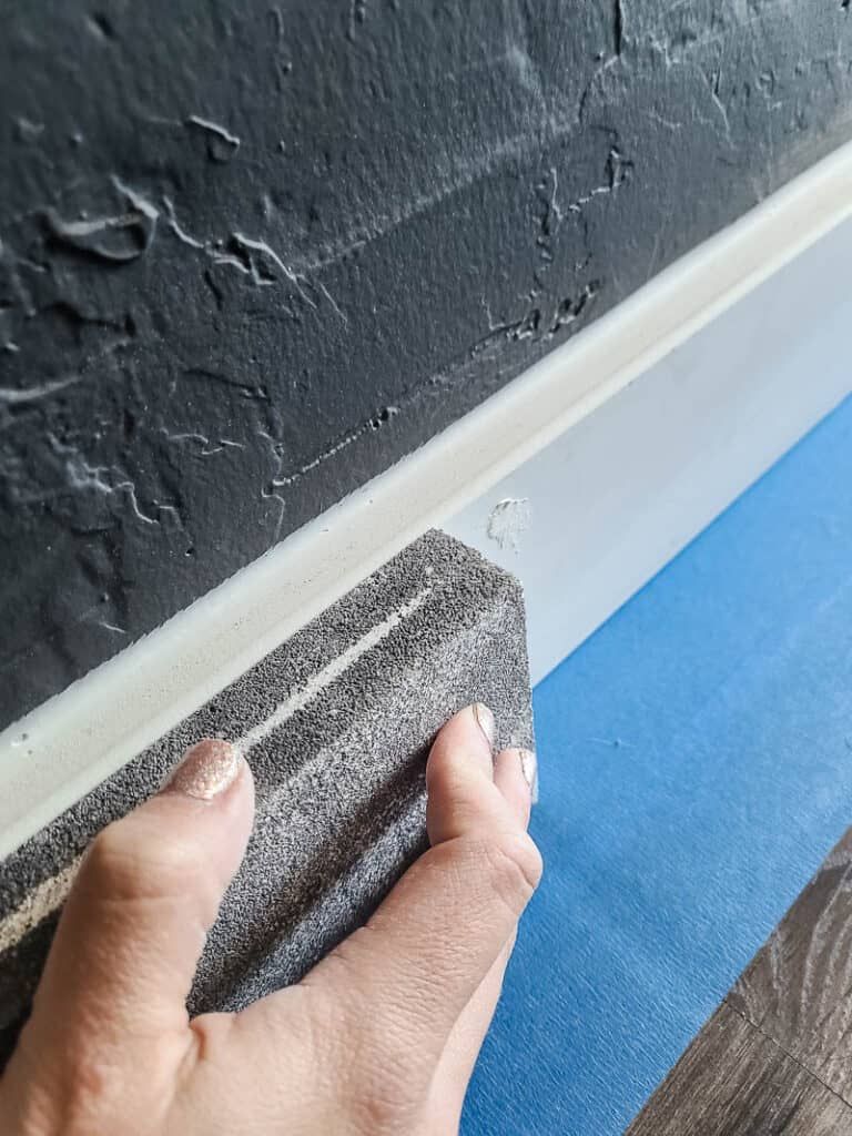 Close up of woman sanding the baseboard with sanding sponge before painting