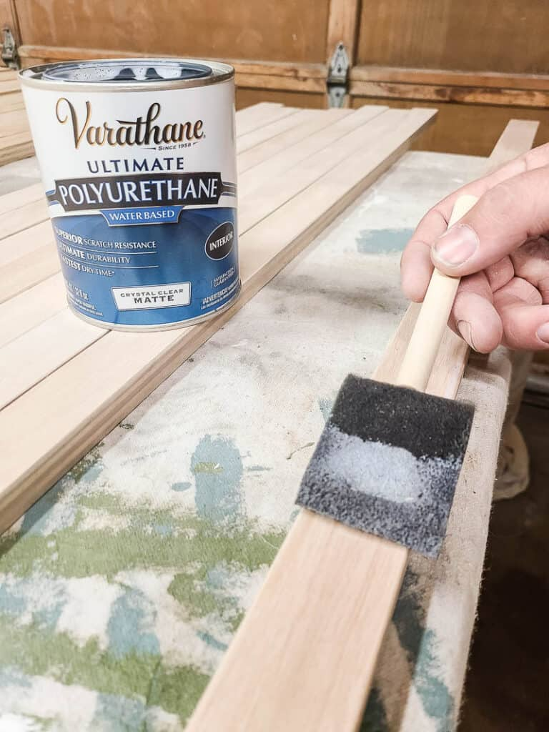 Can of matte polyurethane on top of slat of wood and man brushing matte polyurethane using foam brush onto the wood slat to seal the wood