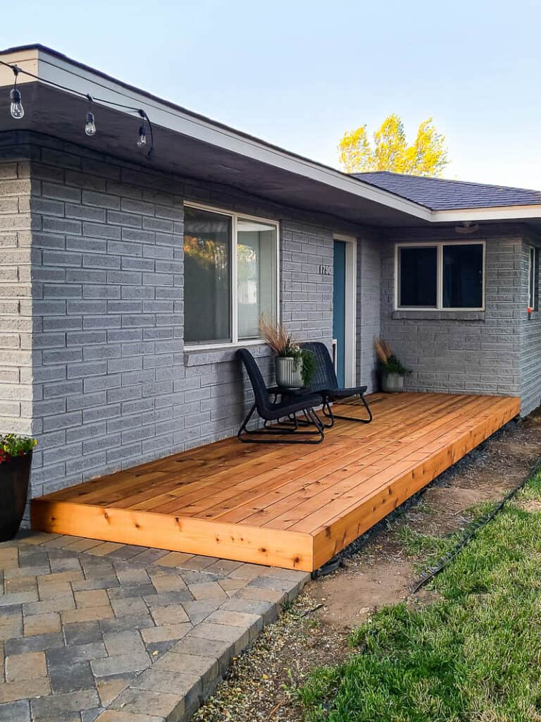 Full view of backyard with wood deck, chairs, center table, plants, windows and back door