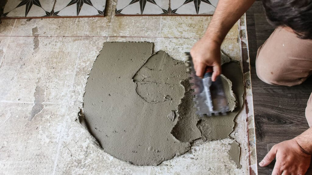 Man applying mortar on the floor with notched trowel
