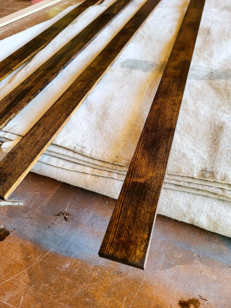 Pieces of thin lattice wood laid at the back of a drop cloth before installing around tapestry to create frame pieces