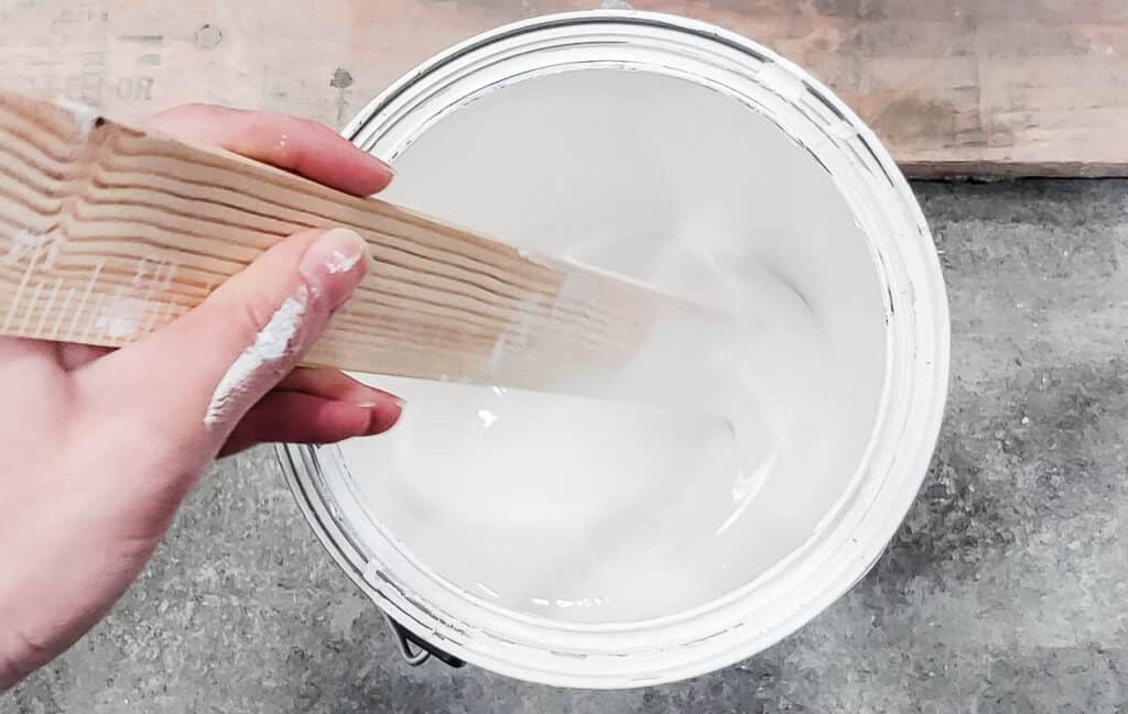Shake the can of wall paint and open with a paint can opener (or a screwdriver). Next, take a stir stick and stir the paint well. This step is important because the colors and additives in the paint tend to separate and settle when it's been sitting.