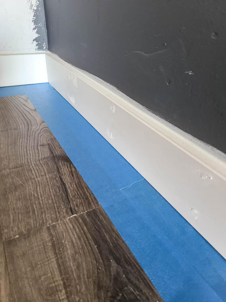 Patched nail holes in baseboards and painter's tape on the floor