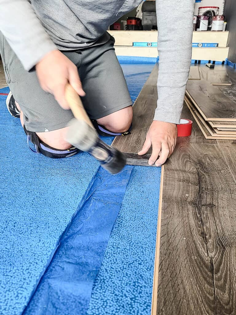Man holding hammer attaching the laminate floors tightly together on top of the underlayment