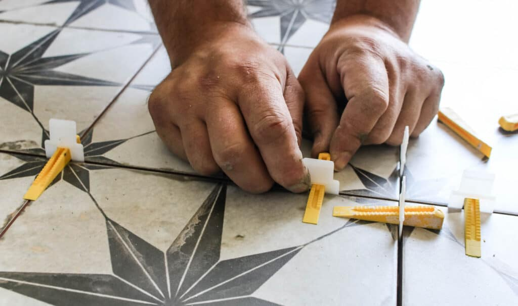 The white part of the spacer goes at the end of the tile and tucks underneath the tile. Then the yellow wedge slides into the hole of the spacer and clicks into place while pushing the tiles down to ensure they are level with each other.
