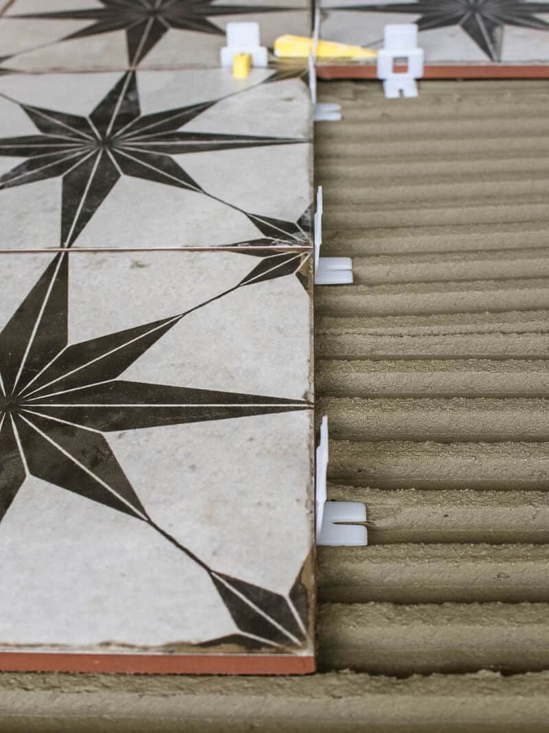 These clip and wedge spacers not only give you the right spacing between your tiles, which you'll grout later - but they also help keep the tiles level with each other.