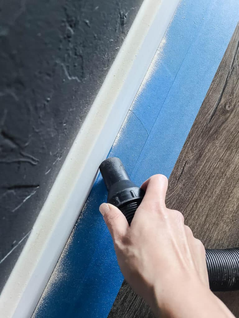 Close up of woman vacuuming the sanding dust from the corners of baseboards