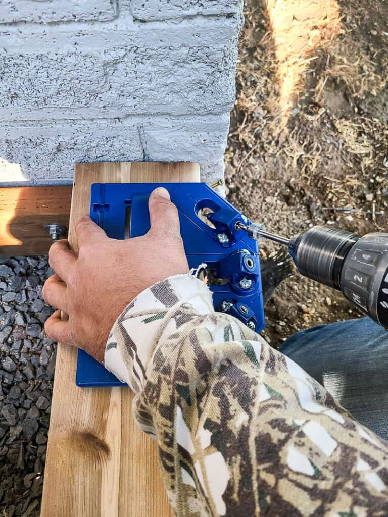 Man attaching wood corner with screws using deck jig and drill using the angled drill guide