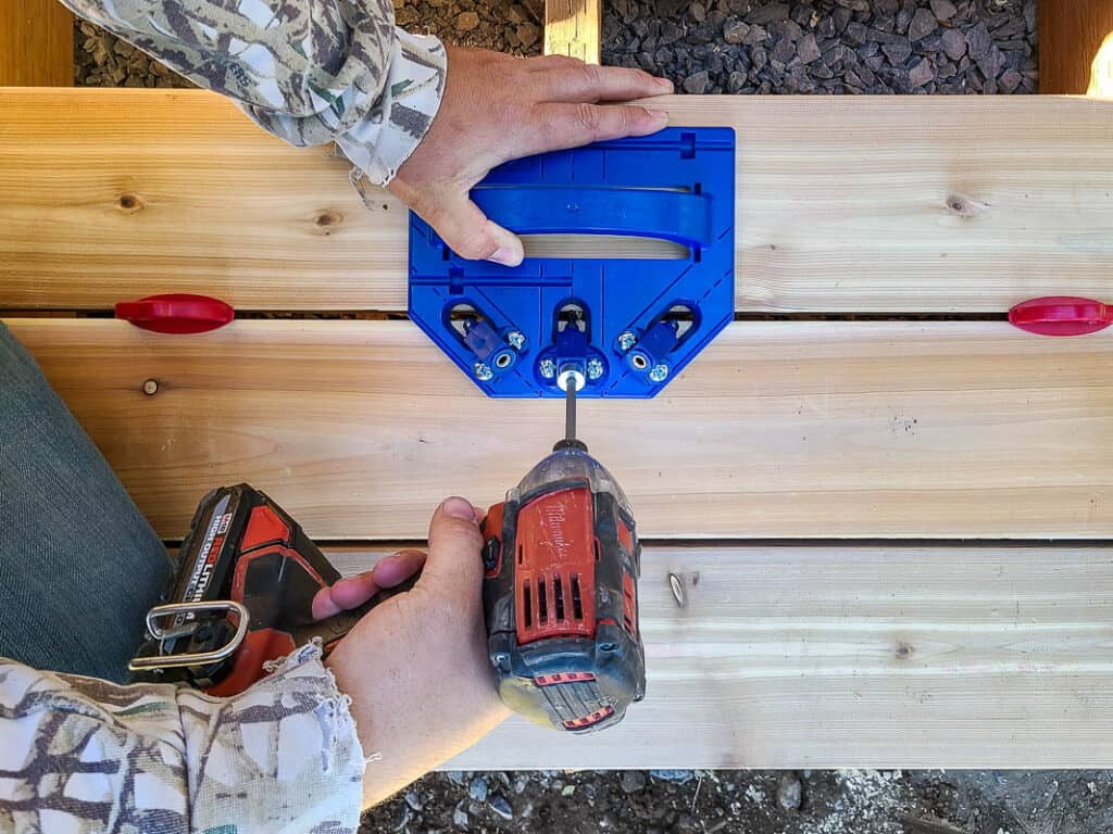 Man laying deck boards using drill and deck jig
