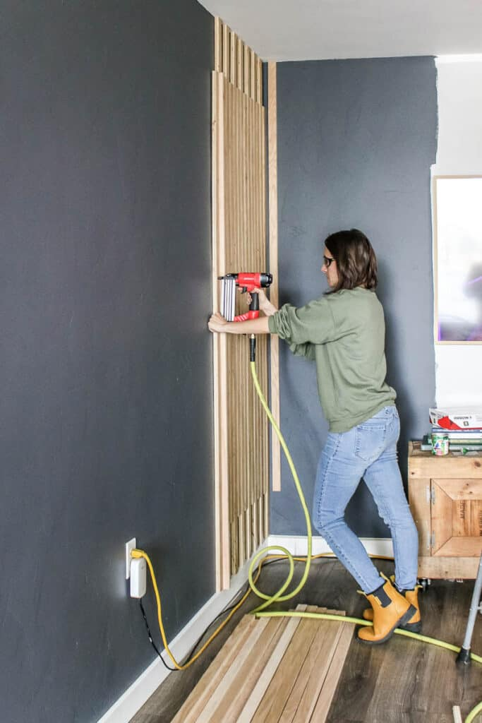 Woman nailing a wood slat on the wall with wood slats on the floor