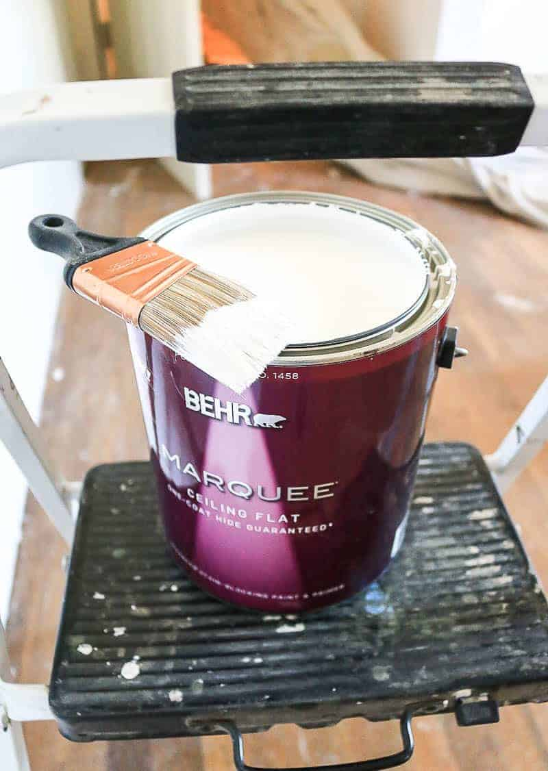 can of white flat ceiling paint sitting on step stool with a paint brush laying on top of it