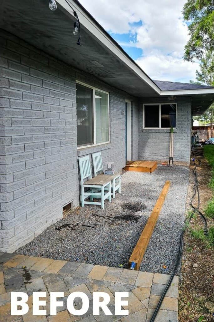 View of the backyard showing the landscape fabric and gravel in the area with two wooden chairs before the makeover