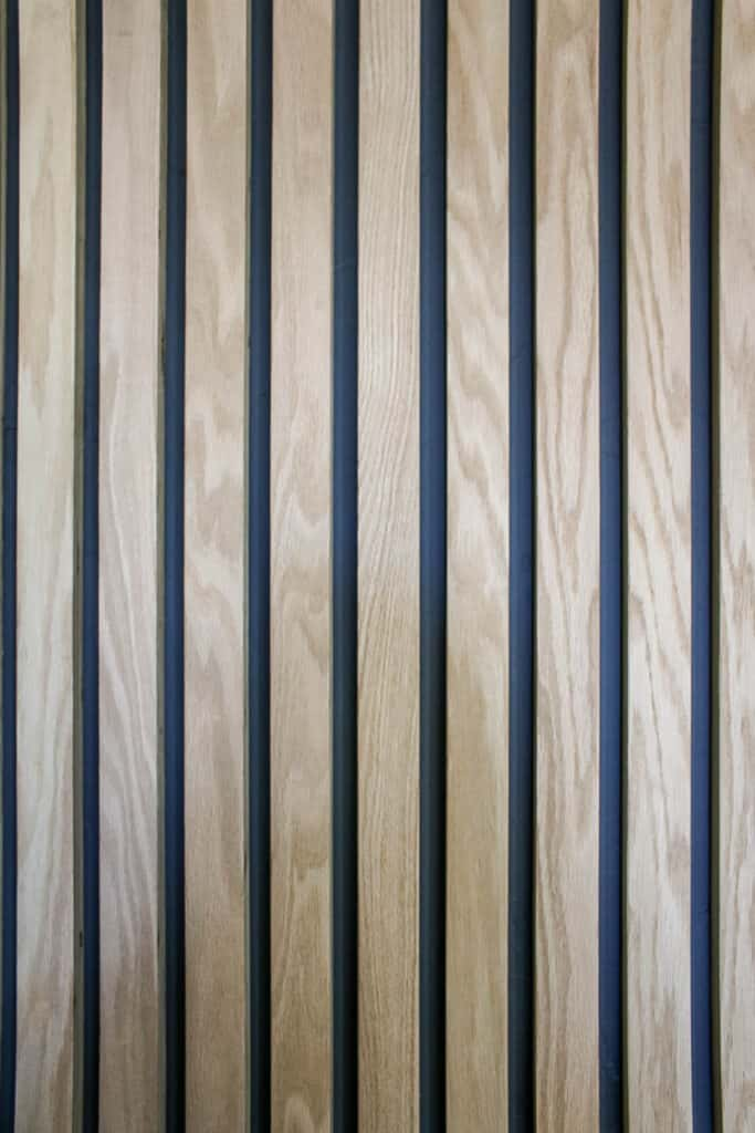 Close up of vertical wood boards on the wall with dark gray paint behind