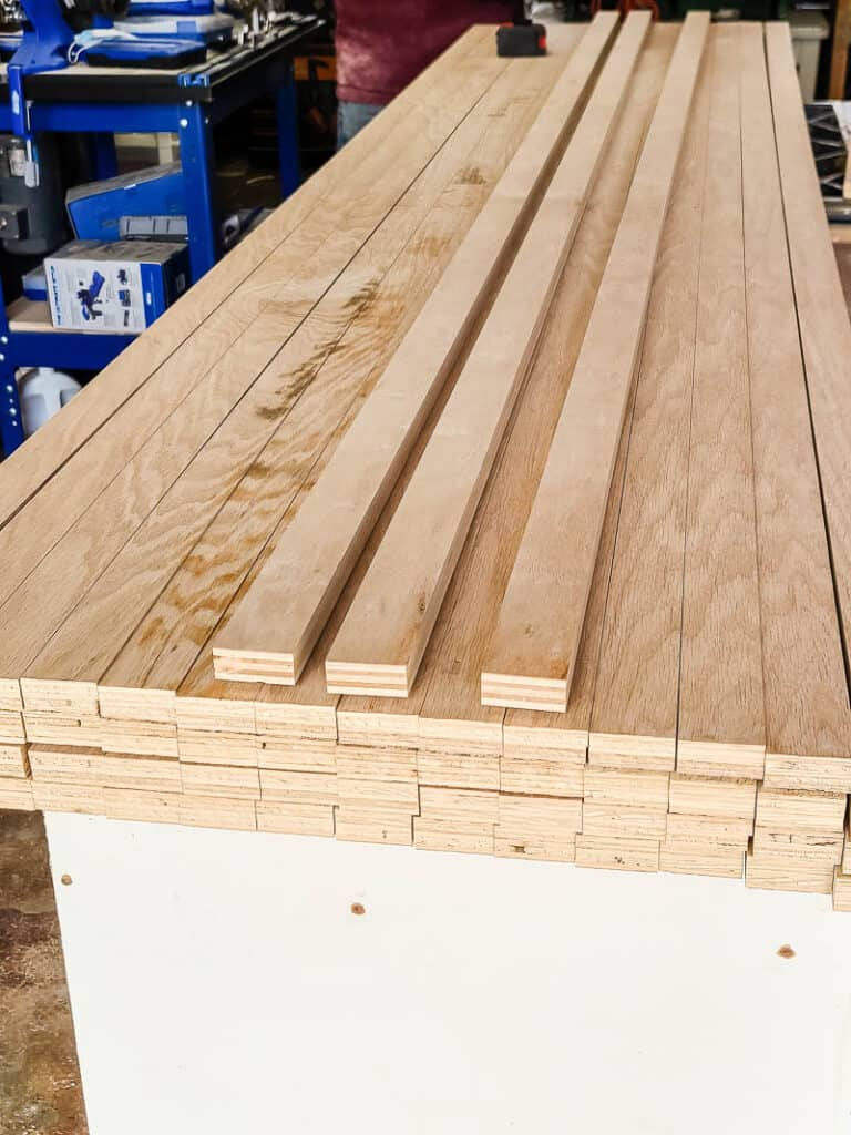 slats of wood on the table before being installed on the wall