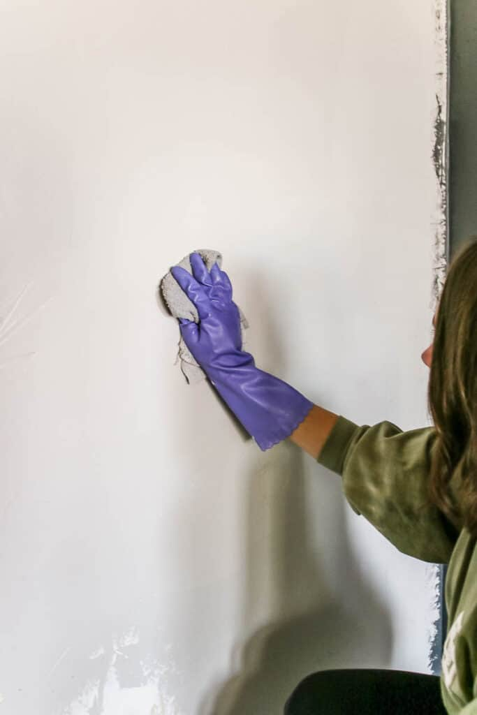 Woman wearing gloves wiping the wall with wet cloth
