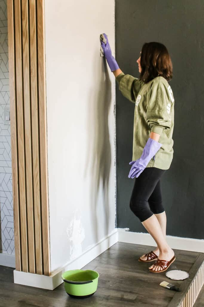 Woman wearing gloves cleaning the wall with a cloth before painting