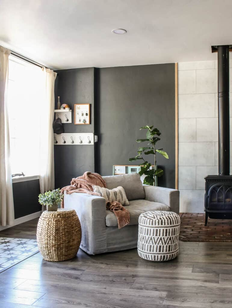 This image has an empty alt attribute; its file name is large-gray-arm-chair-with-with-boho-ottoman-and-wicker-side-table-in-living-room-771x1024.jpg