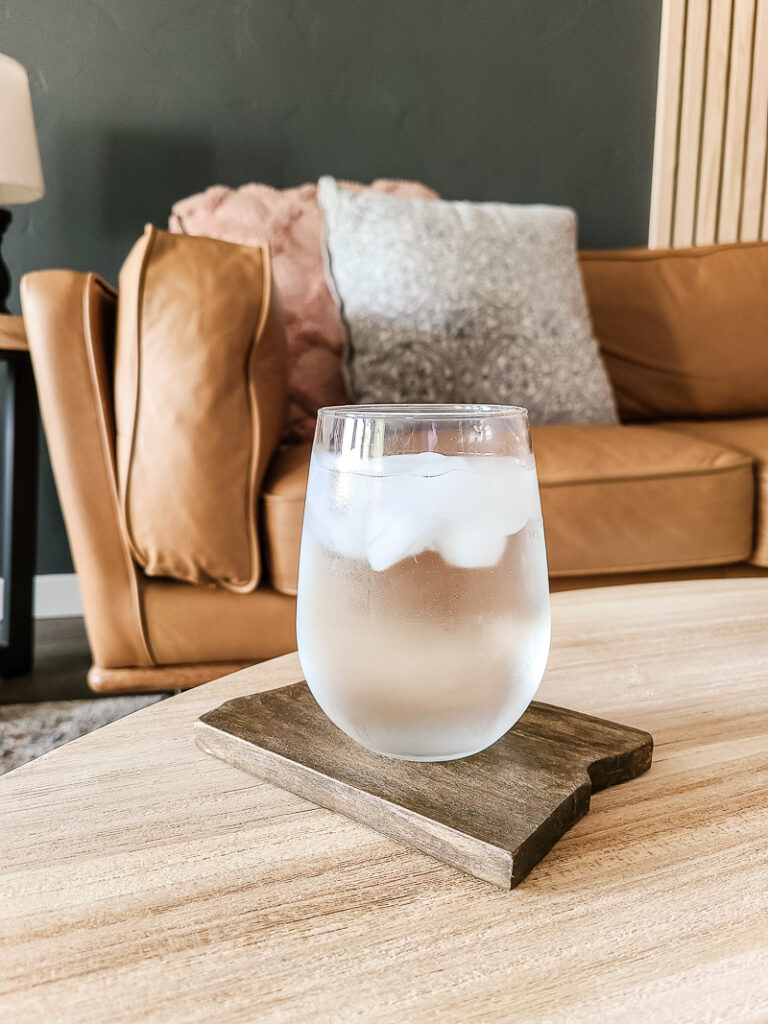 Glass of ice cold water on top of the diy wood coaster with state shape on the center table