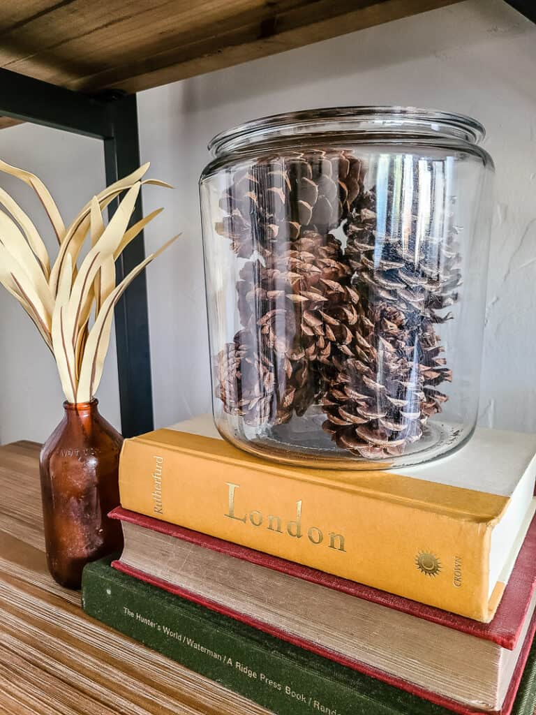 apothecary jar of pinecones and other fall decor