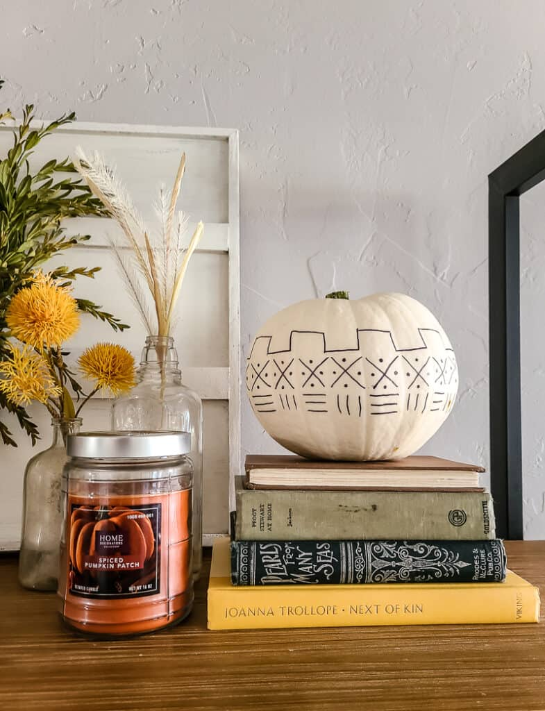White pumpkin with mud cloth pattern displayed with books and fall decor
