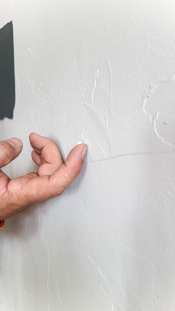 Finger with a pea sized spackling covering the nail hole in the white wall