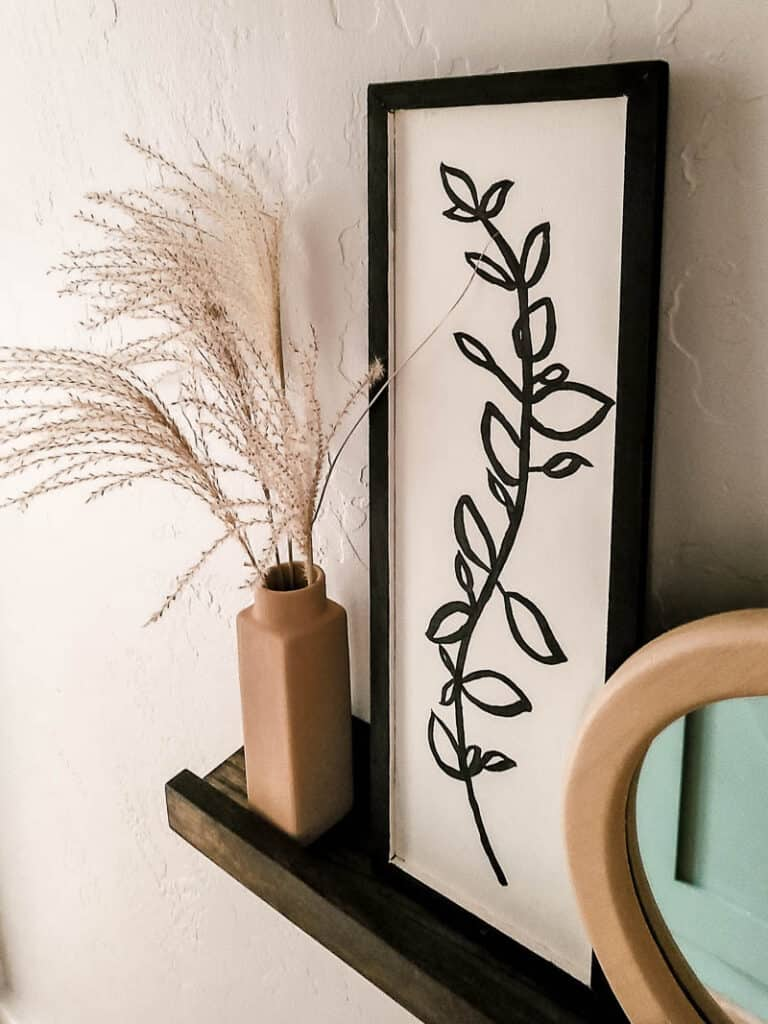 Boho floral line art after makeover placed in a hanging shelf beside a vase with dried flower and mirror