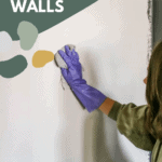 Woman wearing gloves wiping the wall with a cloth