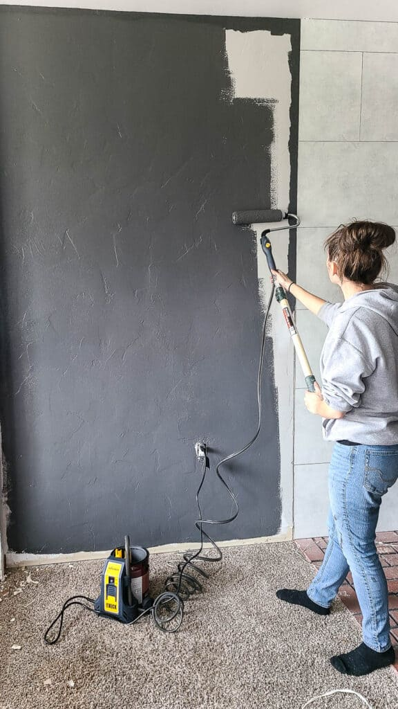 Full view of woman painting the wall using multi-room powered roller paint almost finished