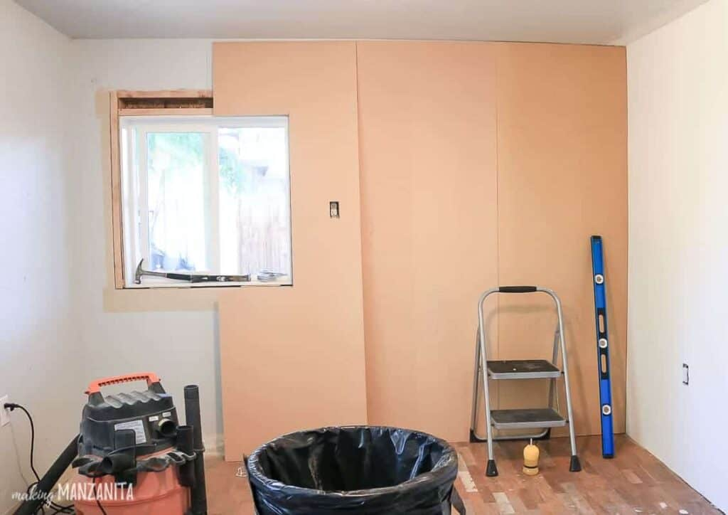 MDF wood covering the wall with ladder, ruler, garbage bin and saw