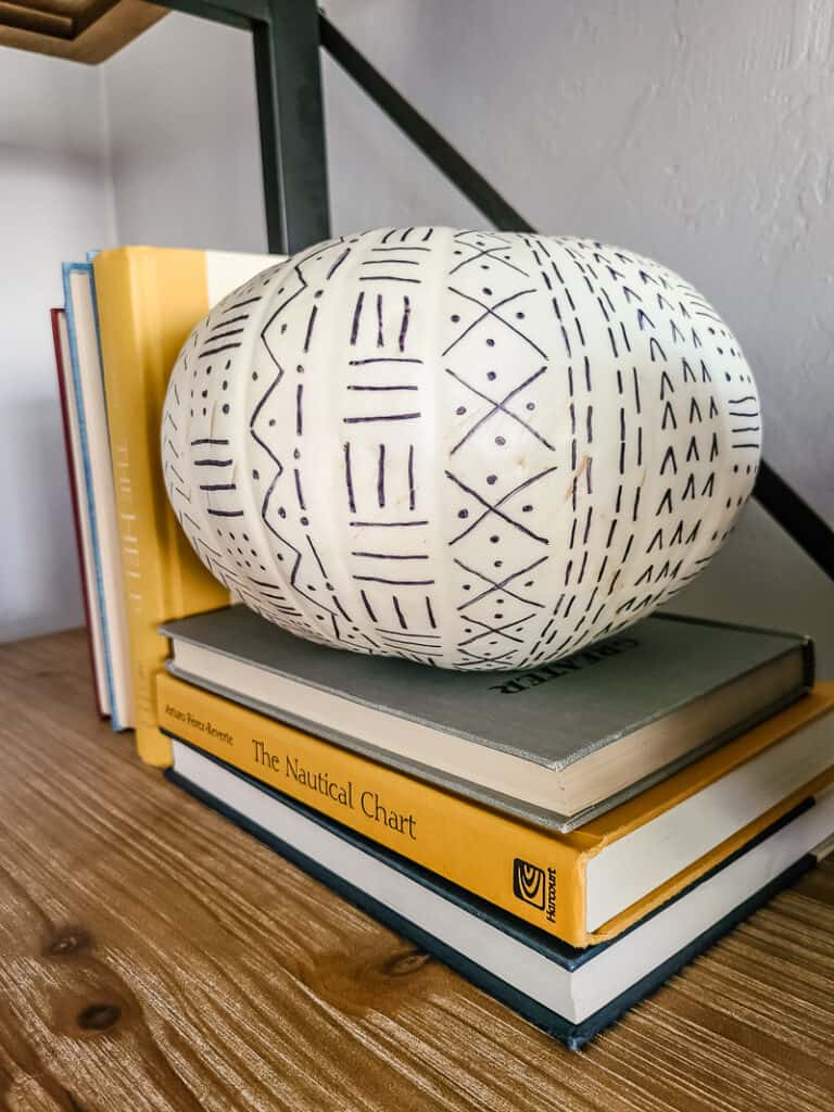 white pumpkin with black mud cloth design displayed with books