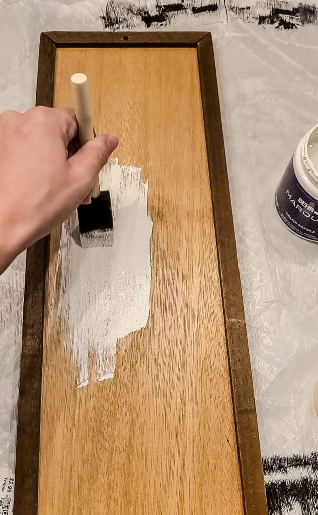 Woman painting the old thrift store sign's back with off-white paint using foam paint brush